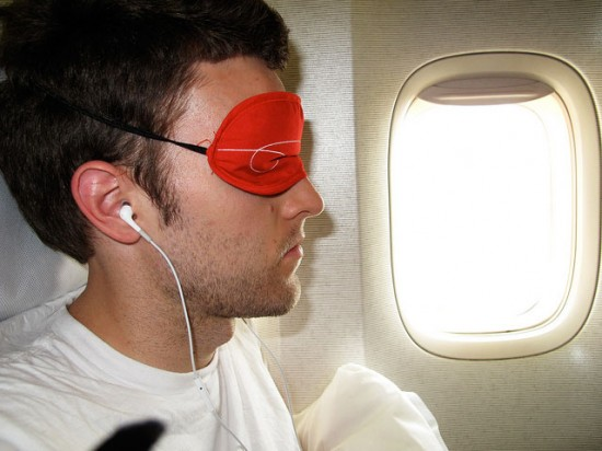 Man wearing an eye mask on a plane