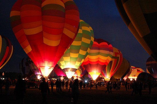 Hot air balloons glow against the night sky